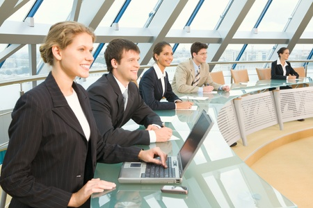 Businesspeople sitting at the round table in large light conference hall with glassy walls discussing important questions photo