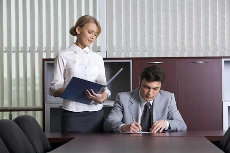 director de escuela: Secretario inteligente est� dando documentos a su jefe para la firma