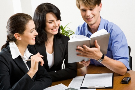 Portrait of three  professionals looking at male�s notepad  photo