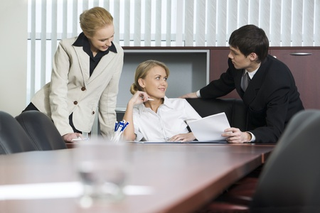 persuading: Brunette businessman is persuading two flirting businesswomen to sign an agreement