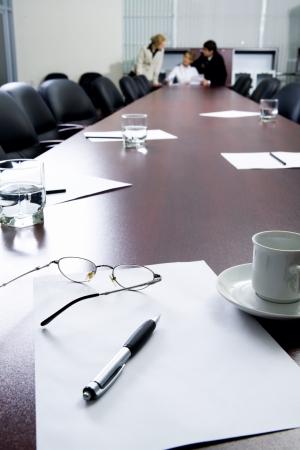 office break: Gafas de izquierda, notas y papel en la gran mesa de negociaci�n y tres empresarios en el fondo de continuar su discusi�n