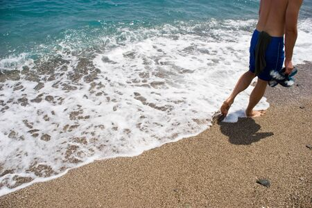 going places: Image of man walking along seashore with surging wave by his legs