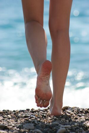 Close-up of slim legs of female walking down pebbles over blue sparkling background photo