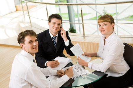 Photo of successful co-workers gathered around table and looking at camera during meeting photo