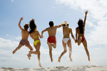 barefoot teens: Rear view of friends holding by hands and jumping on sandy beach against sky Stock Photo