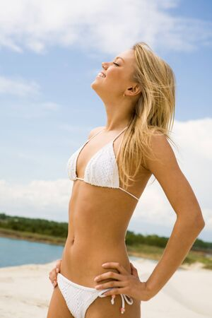 Portrait of pretty blonde in white bikini enjoying summer day on the beach