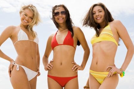 traje de bano: Retrato de tres ni�as delgadas en bikini sonriendo a la c�mara en la playa