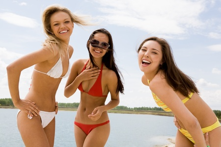 excitement: Portrait of three slim girlfriends in bikini laughing at camera on hot summer day Stock Photo