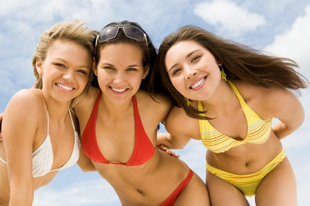women in bikini: Portrait of happy girls in bikini embracing each other and looking at camera