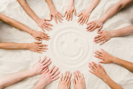 group of hands: Image of several hands on sand in the form of circle with smiling face in center