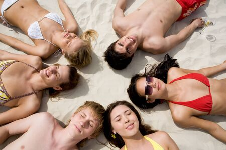 Image of six people resting on the sand  photo