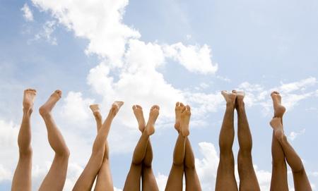 horizontal lines: Fila de piernas humanas sobre un fondo de cielo  Foto de archivo