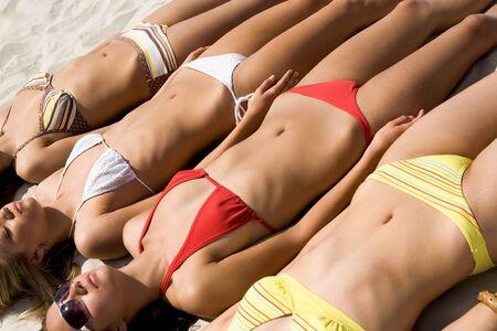 suntan: Photo of several girls lying on sandy beach and getting suntan