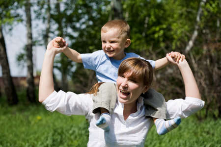 Portrait of joyful woman and playful child on her shoulders having fun outdoors Stock Photo - 8402641
