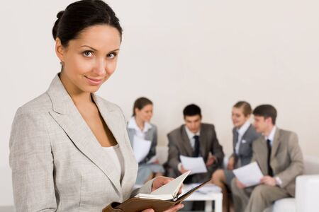 Portrait of smart businesswoman looking at camera on background of working colleagues Stock Photo - 8402155