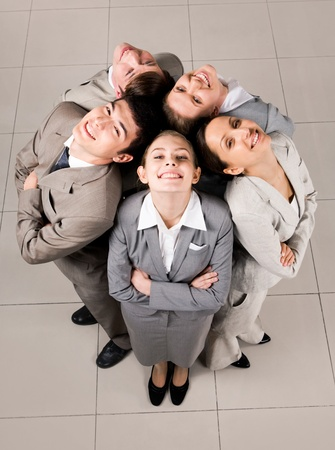 Above view of several business partners looking upwards at camera with their heads close to each other photo