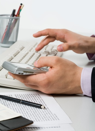 Close-up of male hand pressing keys of smartphone and pushing buttons of keypad photo