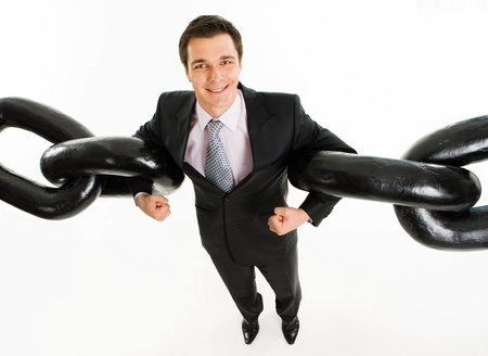 robust: Portrait of powerful businessman holding two sections of huge chain by arms over white background