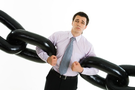 Portrait of helpless businessman holding two sections of huge chain and looking at camera isolated on white background