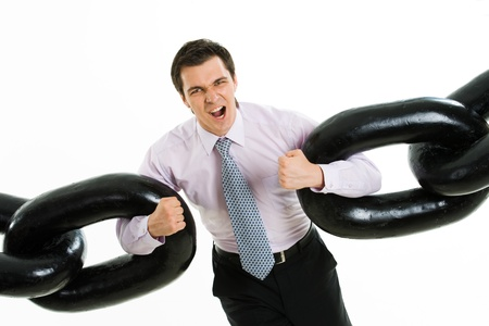 Portrait of frantic businessman with two sections of heavy chain screaming into camera photo