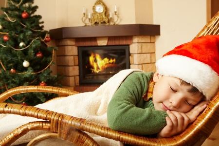chimneys: Photo of cute infant wearing santa cap sleeping in rocking chair under blanket