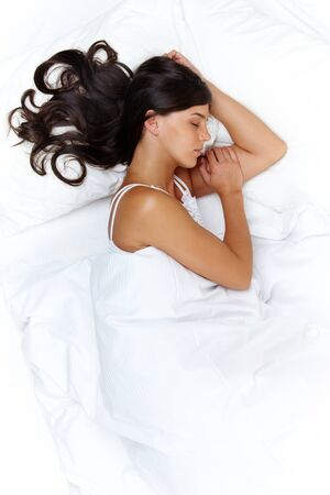 Above view of young beautiful woman sleeping in bed covered with white silky sheet photo