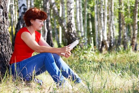 Portrait of middle aged female reading book on grass in natural environment photo