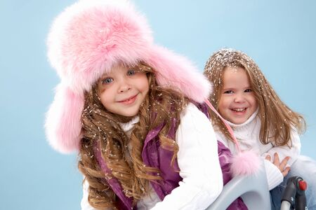 Happy girl in pink furry hat looking at camera with her sister on background photo