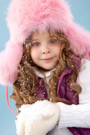 Happy girl in pink furry hat with snow in hands looking at camera photo
