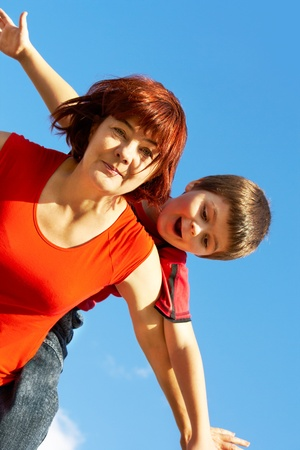 Portrait of middle aged female with her grandson against blue sky photo