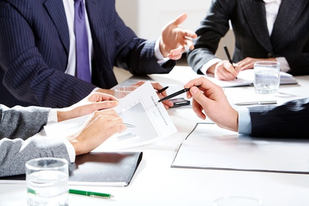 corporate meeting: Close-up of businessman hand with pen explaining a financial plan to colleagues at meeting    Stock Photo
