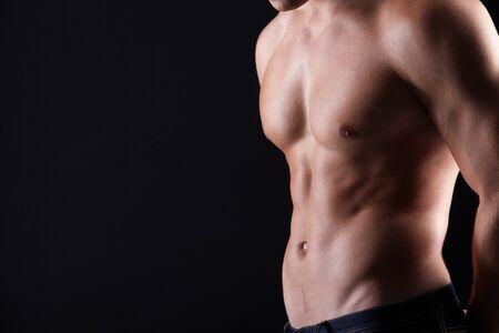 partes del cuerpo humano: Torso de hombre fuerte en jeans contra el fondo oscuro