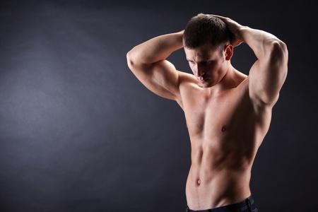 shirtless: Imagen de un hombre sin camisa en jeans mirando hacia abajo con sus manos por encima de la cabeza