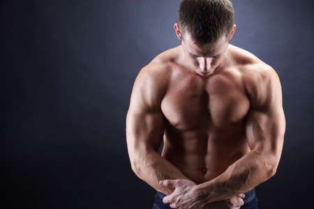 Image of shirtless man looking downwards with his arms crossed by stomach Stock Photo - 8401015