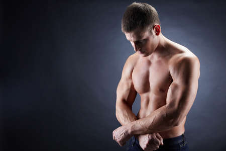 Image of shirtless man looking downwards with his arms crossed by stomach Stock Photo - 8462765