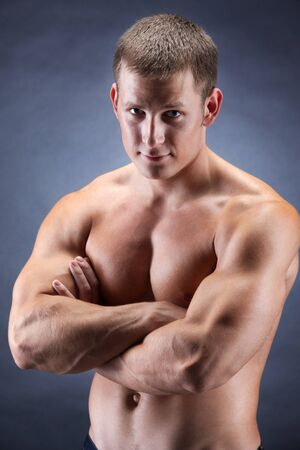 Image of shirtless man with crossed arms looking at camera over dark background Stock Photo - 8405366