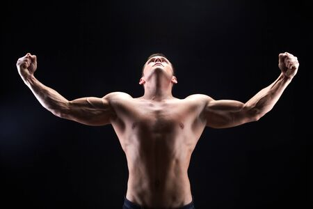 looking upwards: Image of shirtless man looking upwards with raised arms in front of camera