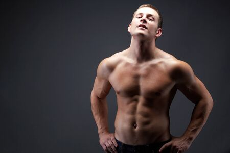 Image of shirtless man in jeans posing in front of camera photo