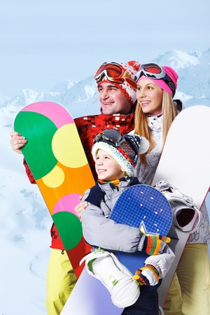 Portrait of happy family with snowboards on winter resort photo