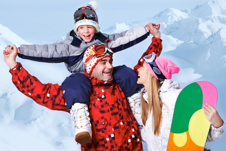 Portrait of happy family with snowboards having fun on winter resort photo