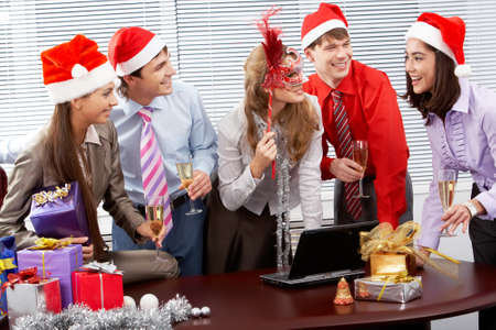 christmas drink: Portrait of happy business people chatting while celebrating Christmas in office