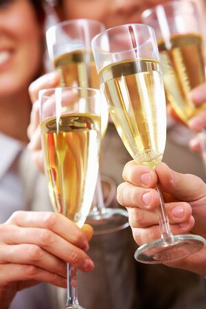 celebration champagne: Image of businesspeople hands holding crystal glasses full of champagne