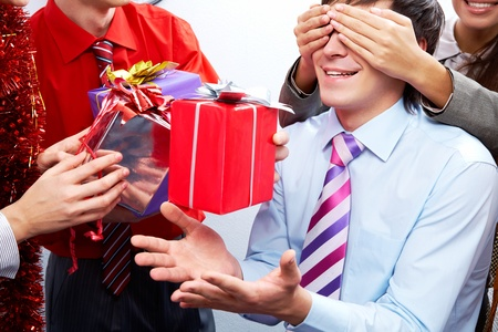 Image of man guessing what present he is going to receive from his colleagues photo
