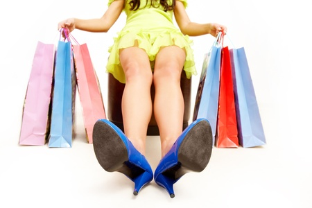 Female stretching legs while sitting with colorful paper bags Stock Photo - 8405454