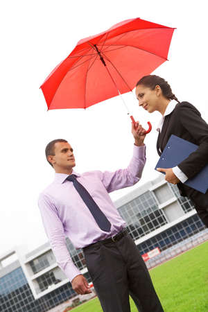 Portrait of handsome man holding red umbrella above female head photo