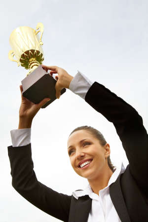 Portrait of happy businesswoman raising championship cup Stock Photo - 8462830