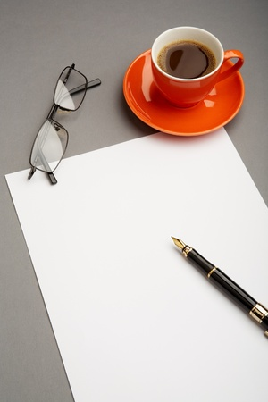 Image of blank paper sheet with fountain pen, eyeglasses and red cup of coffee near by photo