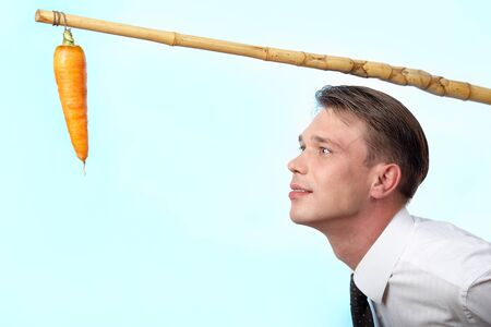 Portret van zaken man kijken naar verse wortel op hoek