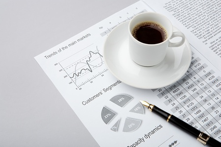 Image of business document with penholder and with cup of coffee on it photo