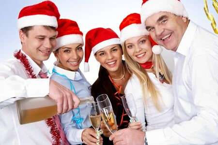 holiday tradition: Portrait of smart colleagues with flutes of champagne looking at camera